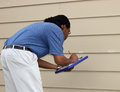Chalk marking hail damage to siding an insurance adjuster marks dings with white and records his findings for a homeowner storm Royalty Free Stock Photo