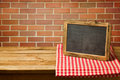 Chalkboard on checked tablecloth copy space for your text or message display over brick wall Stock Photography