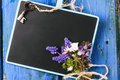 Chalkboard with flowers and key blank bouquet of wildflowers vintage over blue wooden background Royalty Free Stock Images