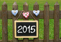 Chalkboard on garden fence or blackboard hanging with quilted heart decorations and green grass Stock Photography