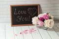 Chalkboard with inscription love you and peonies beautiful bouquet of pink white in the glass vase petals black on the Royalty Free Stock Photography