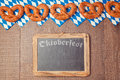 Chalkboard and pretzel on wooden background for Oktoberfest celebration