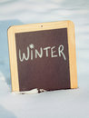 Chalkboard sign in snow with winter written on it Royalty Free Stock Photos