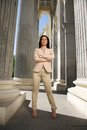 Challenging businesswoman in pose between columns looking at you Royalty Free Stock Photo