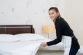 Chamber maid making bed in a hotel room Stock Image