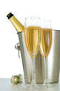 Champagne bottle in bucket with glasses of Stock Photo