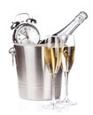 Champagne bottle in bucket two glasses and alarm clock isolated on white background Royalty Free Stock Image