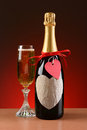 Champagne bottle decorated for valentines day closeup of a a glass of is next to the the has a red ribbon Stock Images