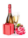 Champagne bottle two glasses gift box and red rose flowers isolated on white background Stock Images