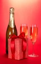 Champagne bottle two wine glasses and gift box the the on a red background Stock Photo