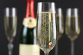 Champagne with bubbles in a glass bottle and more glasses the background Stock Photography