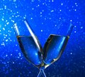 Champagne flutes on blue light bokeh background with space for text Royalty Free Stock Photography