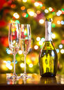 Champagne flutes and bottle on table against Christmas lights Royalty Free Stock Photo