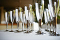 Champagne flutes empty on white linen tablecloth Royalty Free Stock Photos