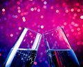 Champagne flutes with gold bubbles on blue tint light bokeh background pair of make cheers space for text Royalty Free Stock Photos