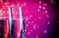 Champagne flutes with gold bubbles on blue and violet tint light bokeh background Royalty Free Stock Photo