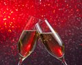Champagne flutes with gold bubbles on red and violet light bokeh background Royalty Free Stock Photo