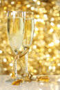 Champagne flutes with golden background Royalty Free Stock Photos