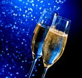 Champagne flutes with golden bubbles on dark blue light bokeh background space for text Stock Image
