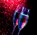 Champagne flutes with golden bubbles on dark blue and violet light bokeh background space for text Stock Images