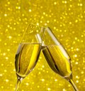 Champagne flutes with golden bubbles on golden light bokeh background make cheers Royalty Free Stock Images