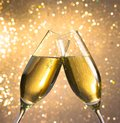 Champagne flutes with golden bubbles on light bokeh background make cheers Royalty Free Stock Photo