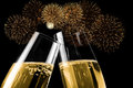Picture : Champagne flutes with golden bubbles make cheers with fireworks sparkle and black background  realistic concept