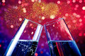 Champagne flutes with golden bubbles on red and purple light bokeh and fireworks sparkle background Royalty Free Stock Photo