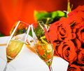 Champagne flutes with golden bubbles on wedding roses flowers background Royalty Free Stock Photo