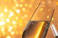 Champagne flutes on golden light bokeh background make cheers with space for text Royalty Free Stock Photo