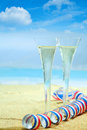 Champagne flutes and a party streamer in elegant fluted glasses colourful red white blue twirled standing on the golden sand Royalty Free Stock Photography