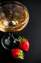 Champagne with strawberries glass of cold on a black background close up Royalty Free Stock Photo