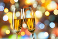 Champagne toast two glasses of toasting against bokeh lights background Royalty Free Stock Photo