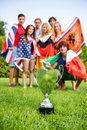 Championship trophy with athletes of various nations on grass in the background Royalty Free Stock Images