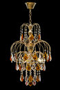 Chandelier for interior of the living room. chandelier decorated with crystals and amber isolated on black background. Royalty Free Stock Photo