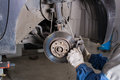 Change the old drive to the Brand new brake disc on car in a garage. Auto mechanic repairing . Royalty Free Stock Photo
