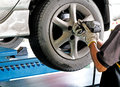Changing car wheel auto mechanic at maintenance repair service station Royalty Free Stock Image