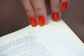 Changing page of book with orange fingernails