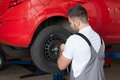 Changing the tire with an impact wrench auto mechanic wheel back view waist up shot in auto repair shop Stock Photo