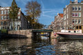 A channel is in amsterdam walk on cutter bridge ahead subzero bridge building along trees above bridge ship along Royalty Free Stock Photography