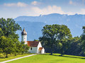 Chapel on grean meadow typical with trees and mountains in bavarian alps Stock Photo
