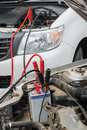 Charge a dead car battery using jumper cables to from another vehicle in raining day Royalty Free Stock Photography