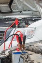 Charge a dead car battery using jumper cables to from another vehicle in raining day Stock Photography