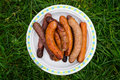 Chargrilled sausages piled on a plate Royalty Free Stock Image