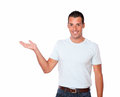 Charismatic guy holding out his right palm portrait of a on white t shirt while standing and looking at you on isolated background Stock Photography