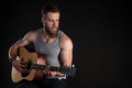 A charismatic man with a beard, playing an acoustic guitar, on a black isolated background. Horizontal frame Royalty Free Stock Photo