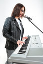 Charismatic young man playing on synthesizer and singing in microphone Royalty Free Stock Photo