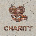 Charity concept on the brick wall word and icon of heart in hand Stock Photo