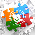 Charity concept on multicolor puzzle word written arround icon of heart in the hand located social Stock Images