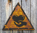 Charity concept on weathered warning sign icon of heart in the hand triangular yellow grange background Stock Photo